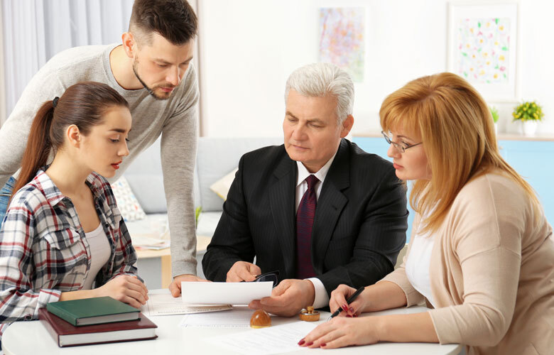 Erbengemeinschaft: Vier Personen an einem Tisch betrachten Dokument